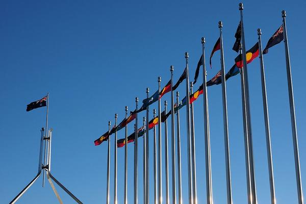 aboriginal torres strait islander and australian flags outside the australian parliament house in july